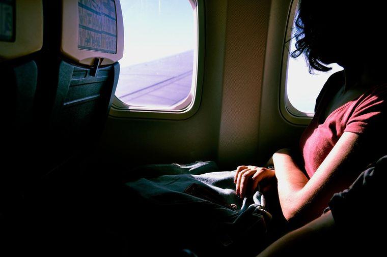 機内から景色を眺める女性