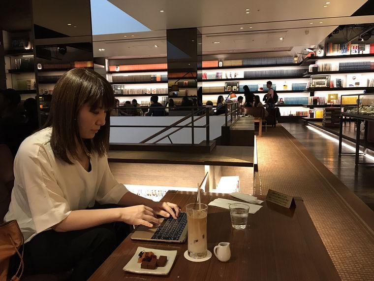 ブックカフェでパソコンを打つ女性