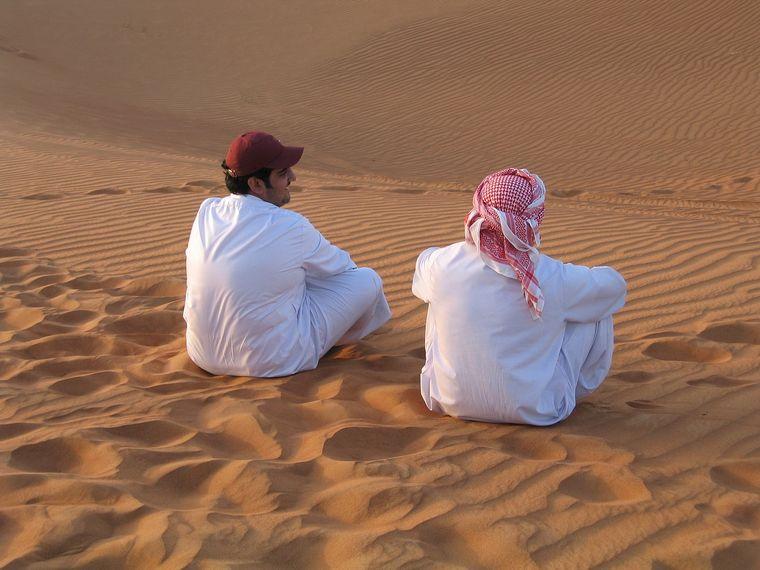 砂漠に座る男性2人